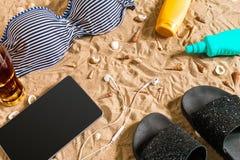 Lato bikini i akcesoria plaży elegancki set Plażowy bikini lata strój i morze piasek jako tło, Odgórny widok Zdjęcie Stock