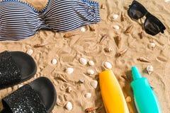 Lato bikini i akcesoria plaży elegancki set Plażowy bikini lata strój i morze piasek jako tło, Odgórny widok Fotografia Stock