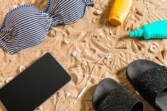 Lato bikini i akcesoria plaży elegancki set Plażowy bikini lata strój i morze piasek jako tło, Odgórny widok Zdjęcia Stock
