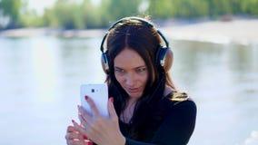 Lato, blisko rzeki, na plaży przy wschodem słońca, piękna kobieta z długim ciemnym włosy, słucha muzyka na hełmofonach od a zbiory wideo