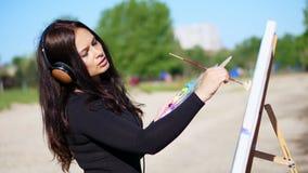 Lato, blisko rzeki, na plaży przy wschodem słońca, piękny kobieta artysta trzyma muśnięcie w jej ręce, rysuje obrazek strzyżenie zbiory