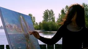 Lato, blisko rzeki, na plaży przy wschodem słońca, piękny kobieta artysta trzyma muśnięcie w jej ręce, rysuje obrazek strzyżenie zbiory wideo