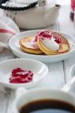 Lato chałupy sera bliny na biel talerzach na drewnianym stole z kawą, mlekiem, kwaśną śmietanką i dżemem, Obrazy Stock