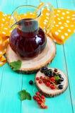 Lato deaktywaci napój - kompot jagody czerni, czerwony rodzynek w dzbanku na jaskrawym tle Obrazy Stock
