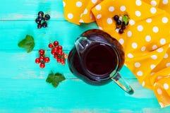 Lato deaktywaci napój - kompot jagody czerni, czerwony rodzynek w dzbanku na jaskrawym tle Obraz Stock