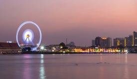 Lato del fiume della ruota panoramica a tempo crepuscolare su paesaggio urbano di Bangkok Immagini Stock