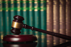Lato del martelletto del giudice davanti ai libri di legge Immagini Stock