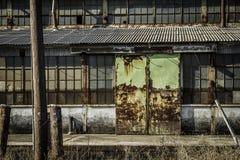 Lato della fabbrica abbandonata con le porte verdi Immagine Stock Libera da Diritti