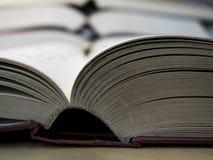 Lato della spina dorsale dei libri aperti sulla tavola di legno in biblioteca Immagine Stock