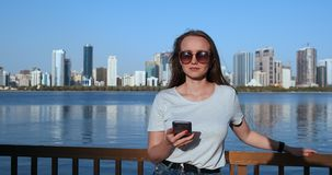Lato dziewczyna na tle dużego miasta uśmiechnięta pozycja z smartphone zbiory