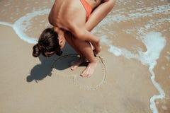 Lato dziewczyny morze Nastolatka remisu serce na piasku Obrazy Royalty Free