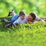 Lato fotografii szczęśliwy ojciec i syn wpólnie kłama na świeżej trawie fotografia royalty free