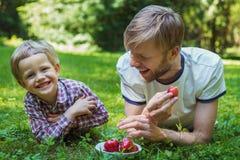 Lato fotografii szczęśliwy ojciec i syn wpólnie kłama na zielonej trawie obrazy royalty free