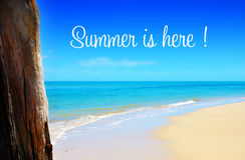 Lato jest Tutaj tekstem nad szeroką piaskowatą plażą z niebieskimi niebami Zdjęcia Stock