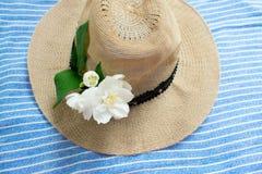 Lato kapelusz i bia?y ja?minowy kwiat na bluebackground obraz stock