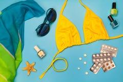 Lato kobiet ` s plaży akcesoria dla twój dennego wakacje i pigułka na błękitnym tle Obraz Stock