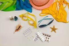 Lato kobiet ` s plaży akcesoria dla twój dennego wakacje i pigułka na białym tle Fotografia Stock