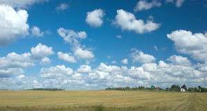 Lato krajobraz z chmurami, łąką i wioską Fotografia Stock