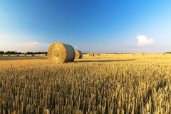 Lato kraju pole z siana niebieskim niebem i belami Fotografia Stock