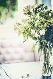 Lato kwitnie wiązkę w szklanej wazie na stole w żywym pokoju z spada płatkami wygodny dom fotografia royalty free