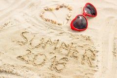 Lato 2016 patroszony na piasku i sercu skorupy z okularami przeciwsłonecznymi Zdjęcia Stock