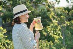 Lato plenerowy portret kobieta z naturalnym napojem robić od truskawki mennicy ziele, kobiety ogrodnictwo fotografia stock