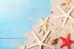 Lato podróży tło od seashell, rozgwiazdy i piaska na błękitnym stołowym odgórnym widoku, Fotografia Royalty Free