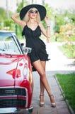 Lato portret elegancka blondynka rocznika kobieta z długimi nogami pozuje blisko czerwonego retro samochodu modna atrakcyjna uczc Fotografia Royalty Free
