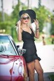 Lato portret elegancka blondynka rocznika kobieta z długimi nogami pozuje blisko czerwonego retro samochodu modna atrakcyjna uczc Obrazy Royalty Free