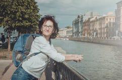 Lato portret szczęśliwy środkowy kobieta turysta z szkłami, ubierający w przypadkowej białej bluzce, błękitny plecak na ona Fotografia Stock