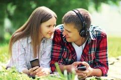 Lato portreta potomstw para kłama relaksować na trawie słucha muzyka w hełmofonach na smartphone zdjęcie stock