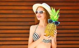 Lato portreta uśmiechnięta kobieta z śmiesznym ananasem w okularach przeciwsłonecznych fotografia stock