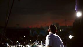 Lato posteriore del DJ in camicia bianca che fila alla piattaforma girevole sul partito di notte dell'aria aperta intrattenimento archivi video