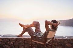 Lato posteriore del giovane che esamina il mare, concetto di stile di vita di vacanze immagine stock