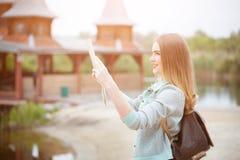 Lato posteriore della ragazza del viaggiatore che cerca giusta direzione sulla mappa, luce arancio di tramonto, viaggiante lungo  immagini stock