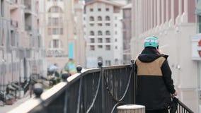 Lato posteriore dello snowboarder in uniforme, soggiorno del casco al recinto del ferro Via, costruzioni Sera nella città video d archivio