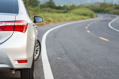 Lato posteriore di nuovo parcheggio d'argento dell'automobile sulla strada asfaltata Fotografia Stock