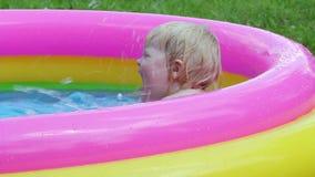 Lato rozrywka - dziewczynki zabawy kąpanie w nadmuchiwanym basenie w podwórzu zdjęcie wideo