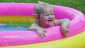 Lato rozrywka - dziewczynki zabawy kąpanie w nadmuchiwanym basenie w podwórzu zbiory