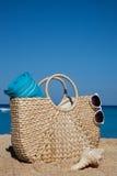 Lato słomiana torba z błękitnymi okularami przeciwsłonecznymi na tropikalnym sa i ręcznikiem Zdjęcia Royalty Free