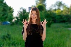Lato w świeże powietrze brunetki azjata młodej pięknej dziewczynie Dwa ręki pokazuje OK Emocjonalna Pozytywna postawa Szczęśliwy obrazy stock