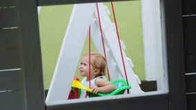 Lato, w ogródzie, ładny trochę jeden roczniak dziewczyny chlanie na huśtawce w boisku zbiory wideo