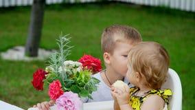 Lato, w ogródzie Czteroletnia chłopiec daje bukietowi kwiaty jego młoda jednoletnia siostra, brat zbiory