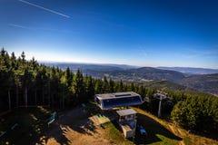 Lato widok na wierzchołek stacji Kouty nad Desnou skłon z zielonymi iglastymi drzewami i zmrokiem - niebieskie niebo fotografia stock