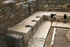 Latrine in Ephesus ancient city. Ephesus which was established as a port, was used to be the most important commercial centre.nEphesus in the UNESCO World Royalty Free Stock Photo