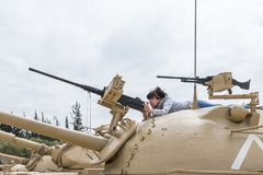 The woman is on the turret of the tank and studies the machine gun on the Memorial Site near the Armored Corps Museum in Latrun, I. Latrun, Israel, April 06 stock photography