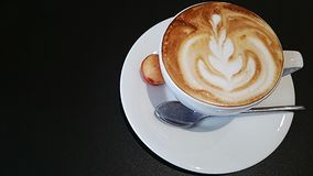 Latte art in a cup with black background Stock Images