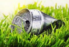 Latta di alluminio sgualcita su un'erba verde Immagine Stock