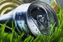 Latta di alluminio sgualcita su un'erba verde Immagini Stock