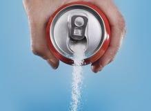 Latta di soda della tenuta della mano che versa una quantità pazza di zucchero in metafora del tenore di zucchero di una bevanda  fotografia stock libera da diritti